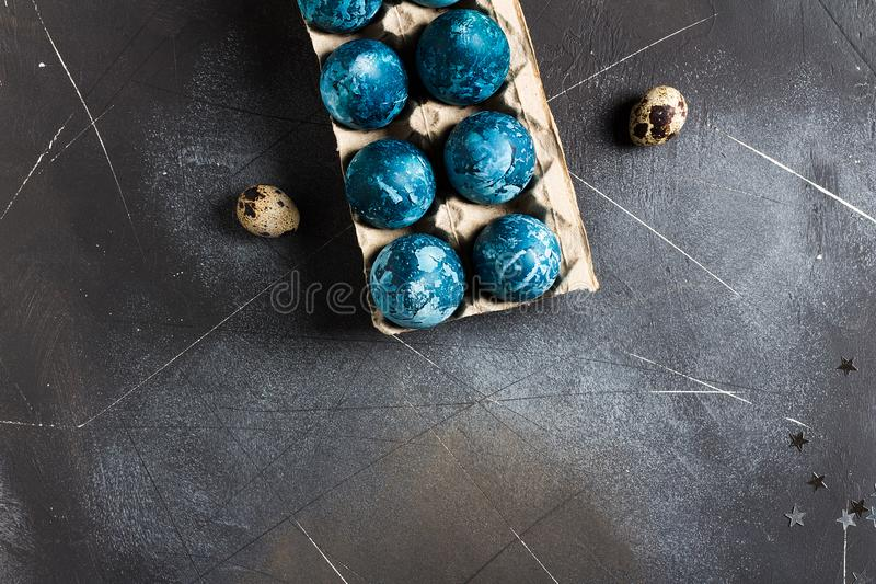 Easter eggs in cardboard packaging painted by hand in blue color royalty free stock images