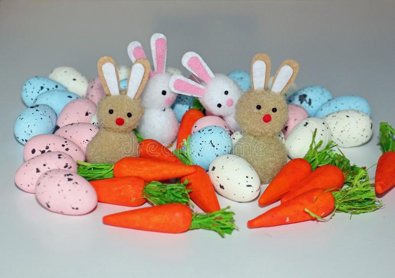 Easter eggs carrots and a group of bunnies royalty free stock photos