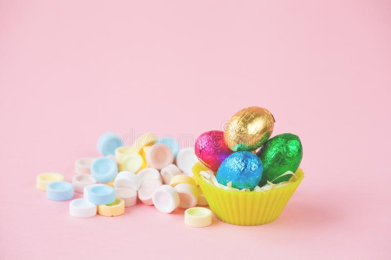 Easter Eggs Chocolates mini basket closeup with drops.  royalty free stock images