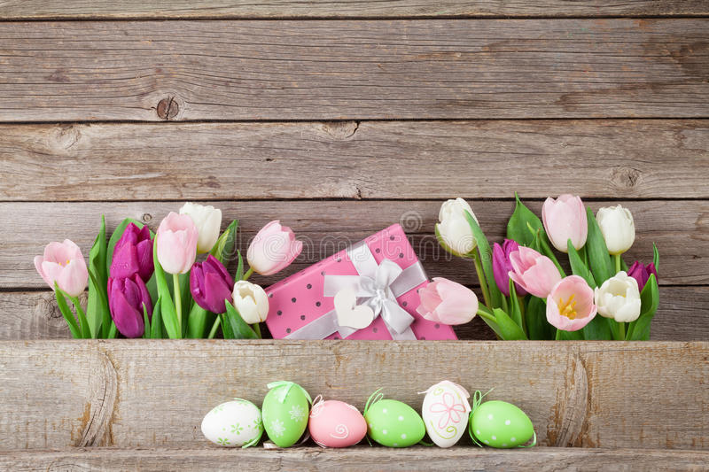 Easter eggs and colorful tulips stock photos