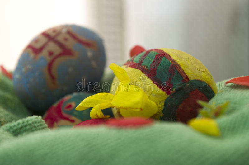 Easter Eggs. Decorated Easter eggs in a basket with cloth and flowers royalty free stock image