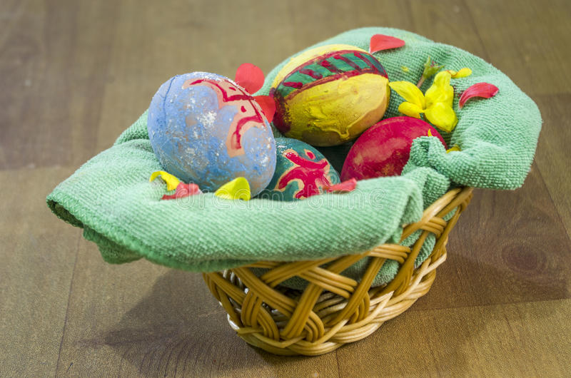 Easter Eggs. Decorated Easter eggs in a basket with cloth and flowers royalty free stock photos