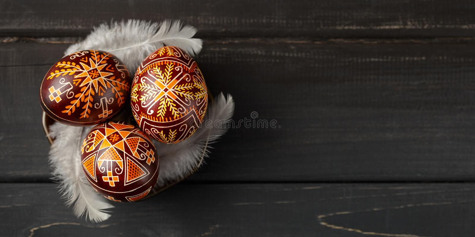Easter eggs decorated with wax resist technique. Pysanky on a small plate, Ukrainian Easter eggs decorated with wax-resist dyeing technique, white feathers stock photography