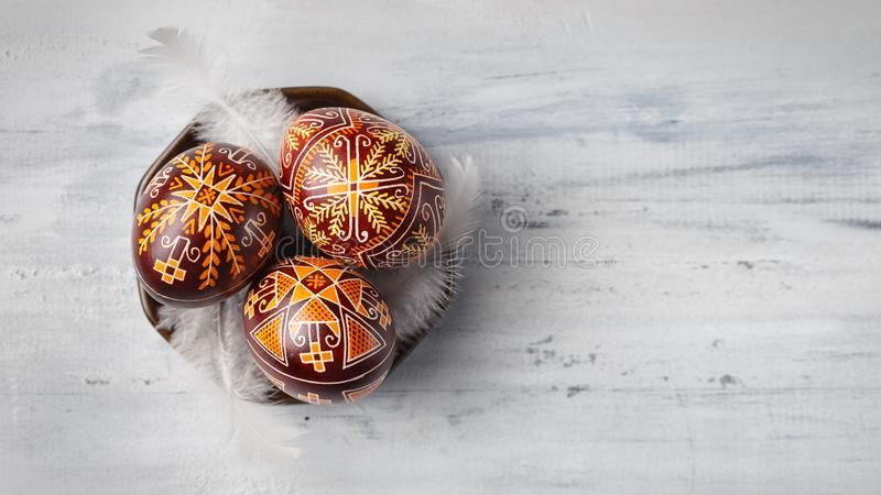 Easter eggs decorated with wax resist technique. Pysanky on a small plate, Ukrainian Easter eggs decorated with wax-resist dyeing technique, white feathers stock photos