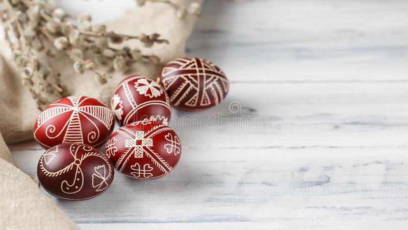 Easter eggs decorated with wax resist technique. Pysanky, Ukrainian Easter eggs decorated with wax-resist dyeing technique, willow tree brunches and linen cloth royalty free stock image