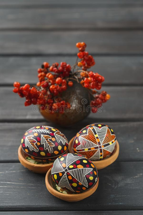 Easter eggs decorated with wax resist technique. Pysanky, Ukrainian Easter eggs decorated with wax-resist dyeing technique, guelder rose on black wooden stock photo