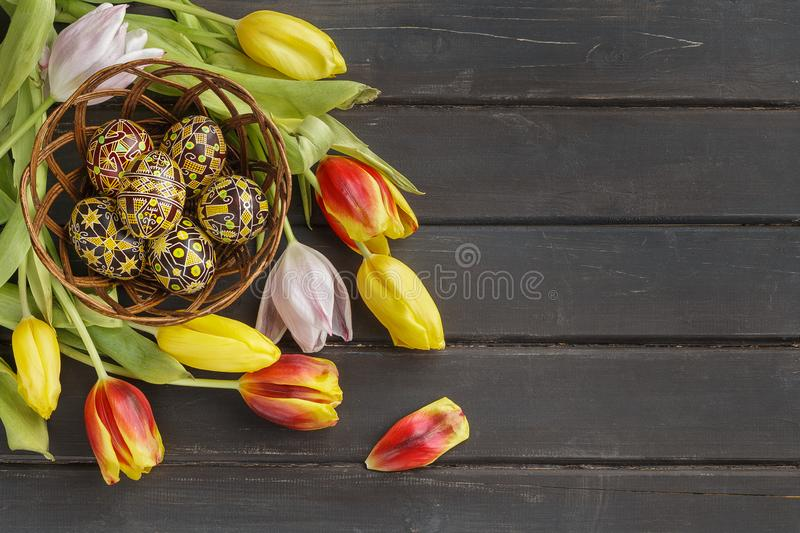 Easter eggs decorated with wax resist technique. Pysanky, Ukrainian Easter eggs decorated with wax-resist dyeing technique, tulip flowers on black wooden stock images