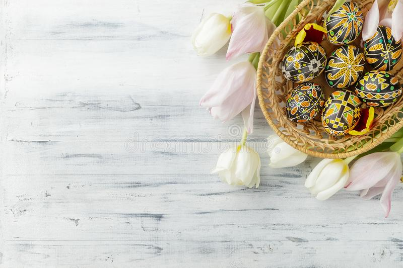 Easter eggs decorated with wax resist technique. Pysanky, Ukrainian Easter eggs decorated with wax-resist dyeing technique, tulip flowers on white wooden stock photo
