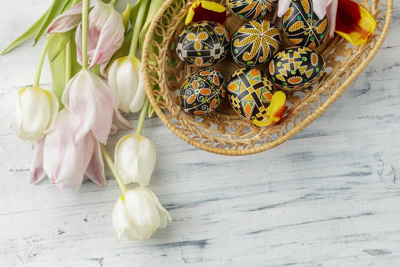 Easter eggs decorated with wax resist technique. Pysanky, Ukrainian Easter eggs decorated with wax-resist dyeing technique, tulip flowers on white wooden stock photos