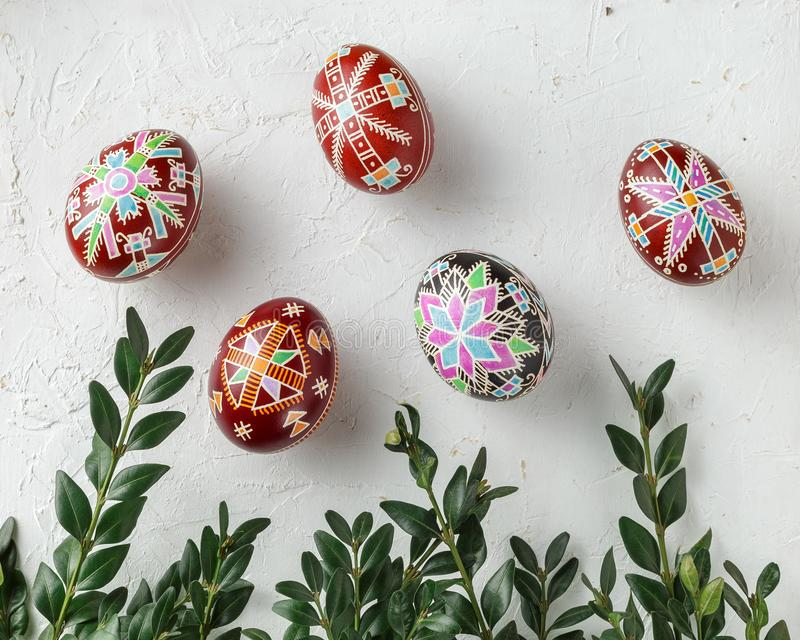 Easter eggs decorated with wax resist technique. Pysanky, Ukrainian Easter eggs decorated with wax-resist dyeing technique, white textured background and Buxus stock image