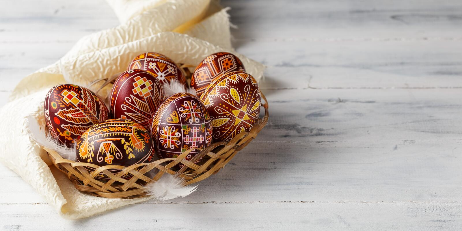 Easter eggs decorated with wax resist technique. Pysanky, Ukrainian Easter eggs decorated with wax-resist dyeing technique, white wooden background, copy space royalty free stock photography
