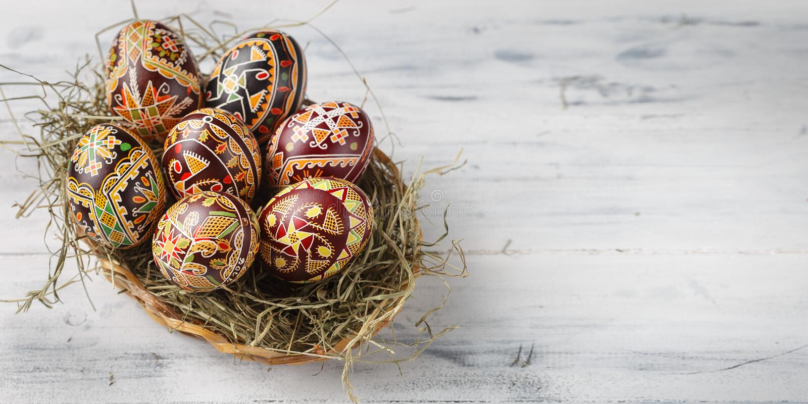 Easter eggs decorated with wax resist technique. Pysanky, Ukrainian Easter eggs decorated with wax-resist dyeing technique, white wooden background, copy space stock images