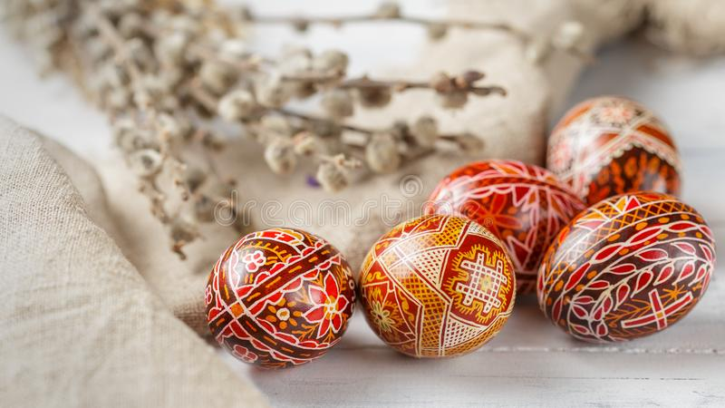 Easter eggs decorated with wax resist technique. Pysanky, Ukrainian Easter eggs decorated with wax-resist dyeing technique, willow tree brunches and linen cloth stock photo
