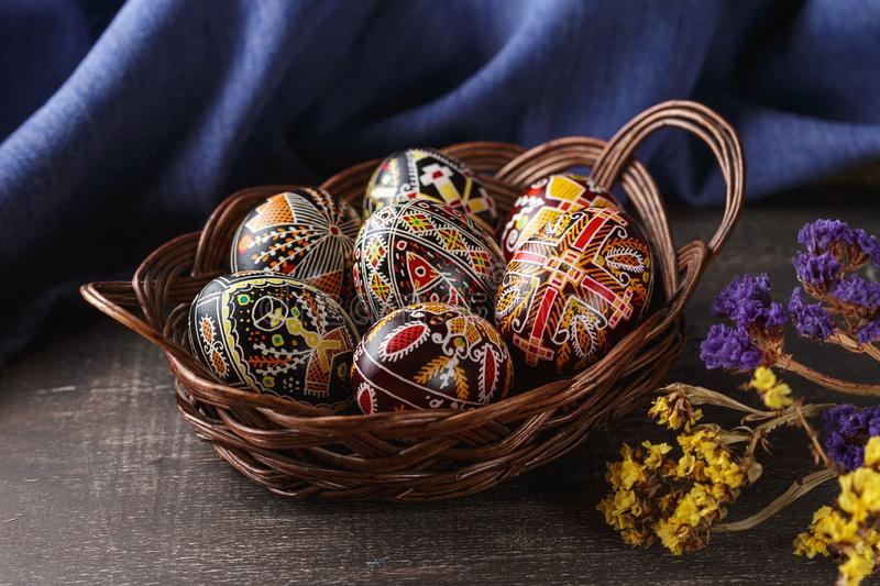 Easter eggs decorated with wax resist technique. Woven dish with Pysanky. Ukrainian Easter eggs decorated with wax-resist dyeing technique, traditional for royalty free stock images
