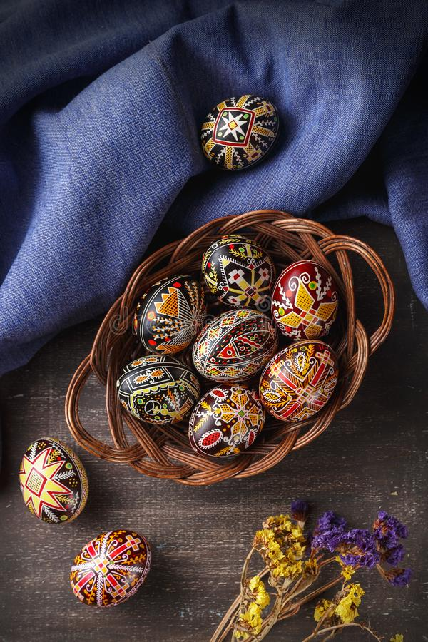 Easter eggs decorated with wax resist technique. Woven dish with Pysanky. Ukrainian Easter eggs decorated with wax-resist dyeing technique, traditional for stock photo