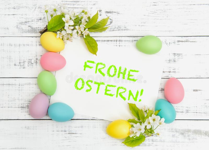 Easter eggs decoration cherry blossoms white paper Frohe Ostern. Easter eggs decoration with cherry blossoms and white paper. Sample text Frohe Ostern - Happy royalty free stock image