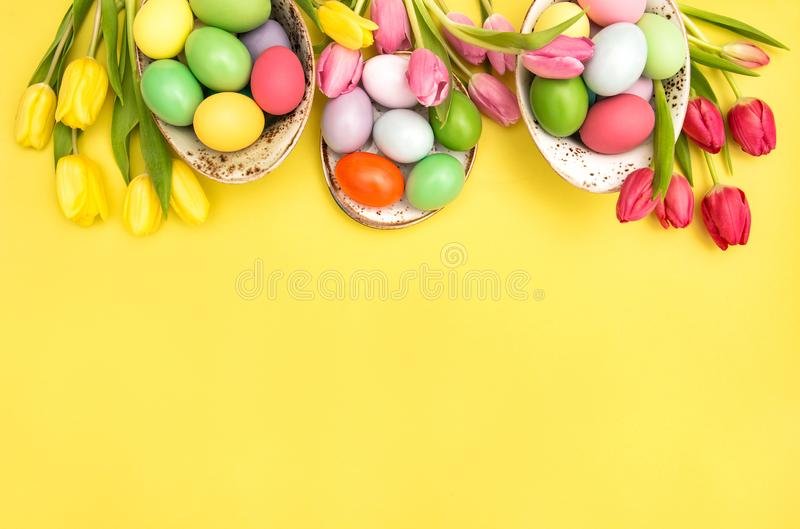 Easter eggs decoration colorful tulip flowers yellow background stock image