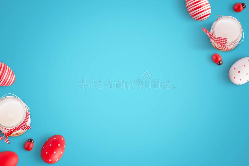 Easter eggs and decorations on blue surface. Flat lay with free space for text in the middle stock images