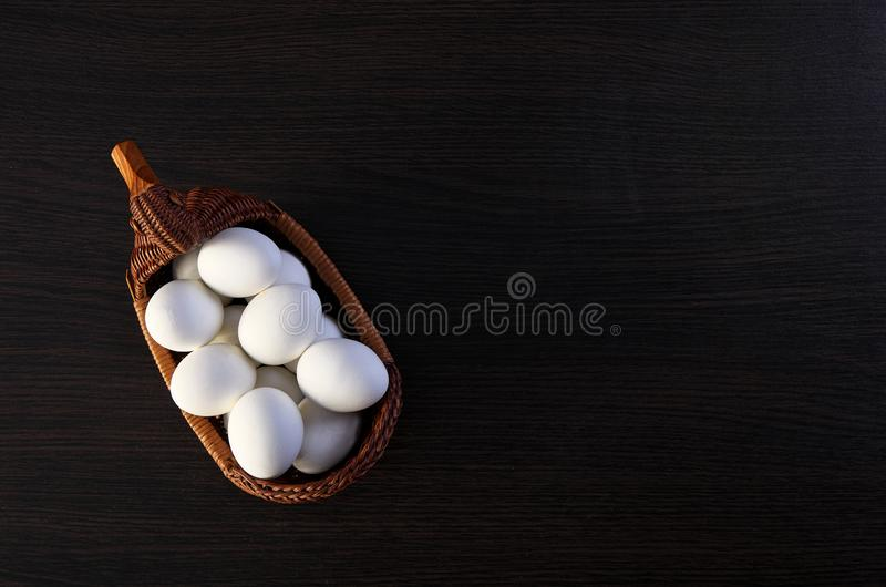 Easter eggs in the Duck basket. wicker basket of straw. festive meal on a dark wooden table stock photography