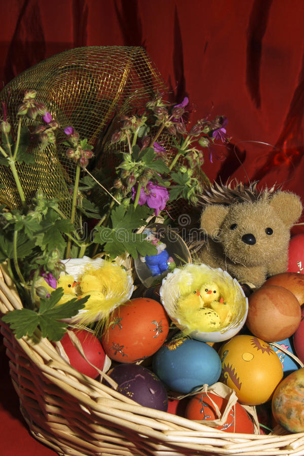 Easter eggs with flowers and a hedgehog in a basket stock images