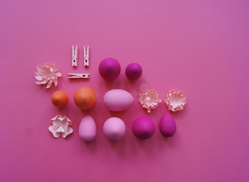 Easter eggs and flowers made of paper on a yellow background. The colors are pink, burgundy, fuchsia and yellow. Spring. stock photo