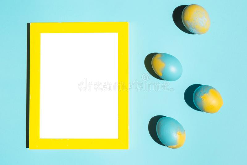 Easter eggs with frame. Colourful Easter eggs with blank frame isolated on blue table royalty free stock photo