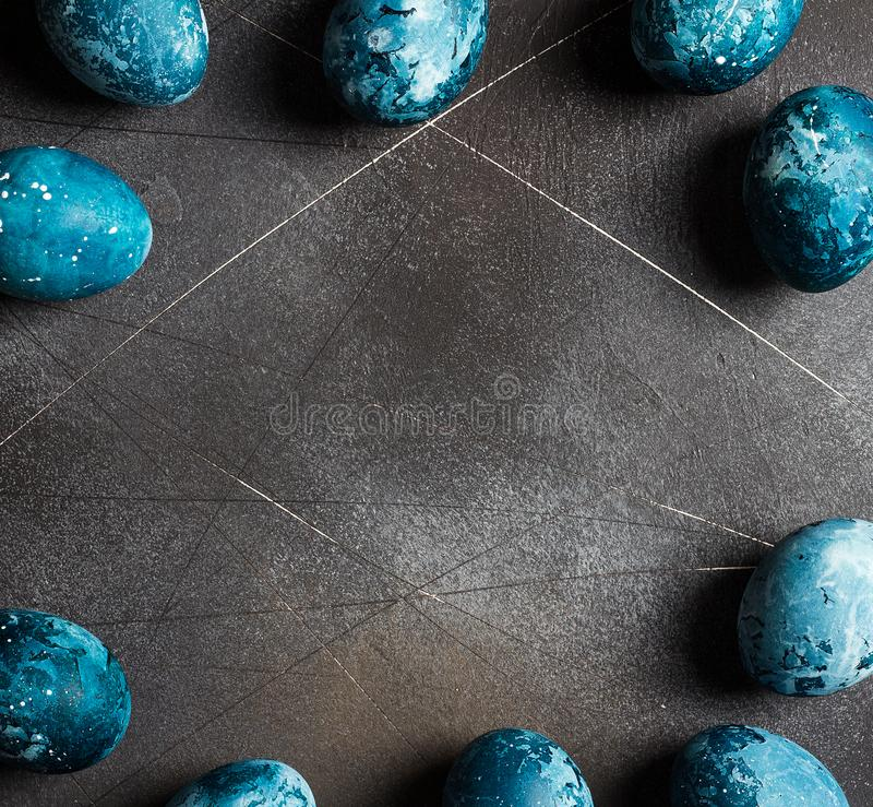 Easter eggs frame painted by hand in blue color on dark background stock images
