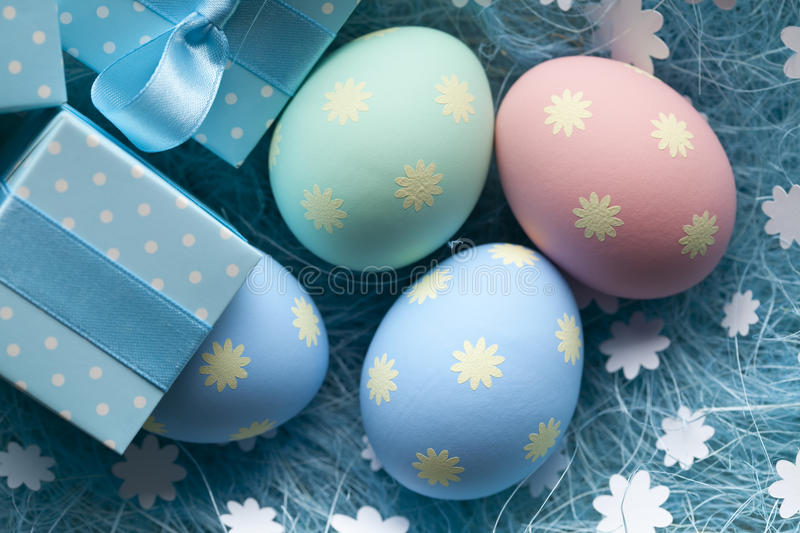 Easter eggs and gift box on blue background stock images