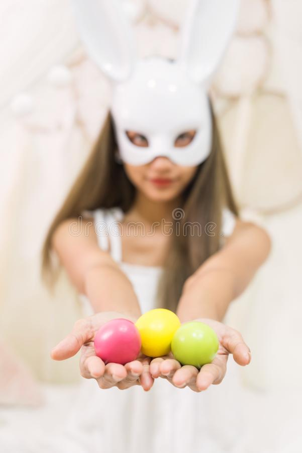 Easter eggs with girl and bunny mask. Closeup colorful easter eggs on brunette attractive woman with white rabbit bunny mask. girl celebrate holiday in home royalty free stock images
