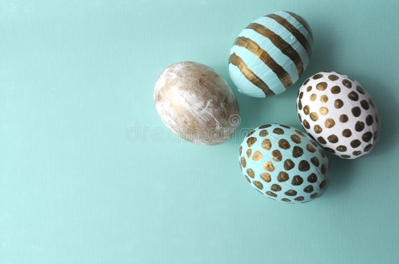 Pretty Easter eggs with gold polka dots and stripes on aqua teal mint background with copy space stock image