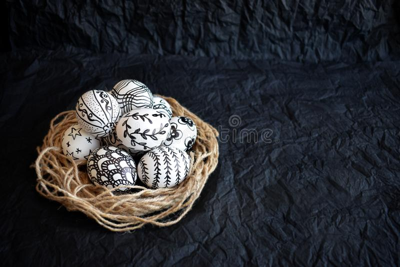 Easter eggs with the hand-drawn different doodle patterns in dec. Orative nest on a black background. Pascha eggs with doodle unusual décor and copy space stock photo