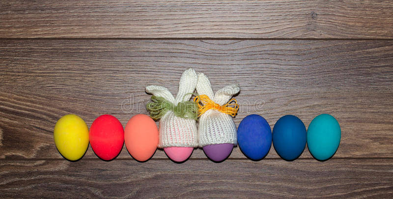 Easter eggs hand painted with knitted bunny hats over wooden background with copy space . Happy Easter stock photo