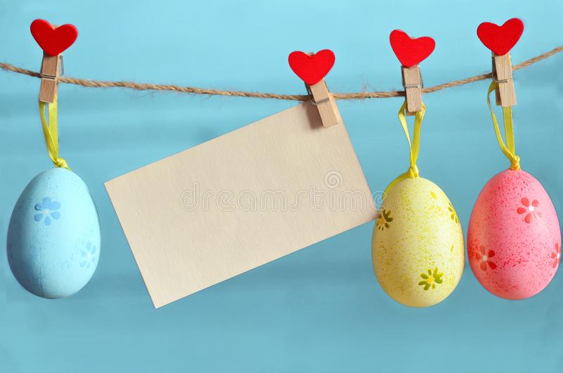 Easter eggs hanging on rope on blue background. Easter eggs hanging on rope on blue wooden background stock photography