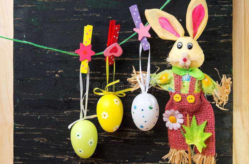 Easter eggs hanging from a string and a bunny stock photos