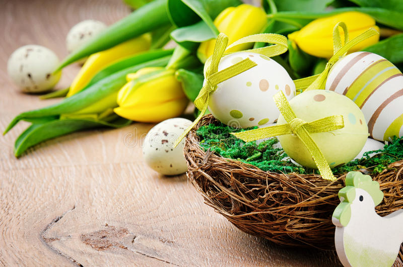 Easter eggs in holiday setting. With yellow tulips stock photo