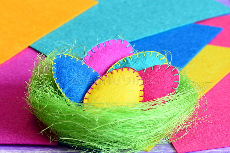 Easter eggs in a nest crafts. Homemade felt Easter eggs in a green sisal nest on colorful felt background. Crafts for decorating a room for Easter. Closeup stock photos