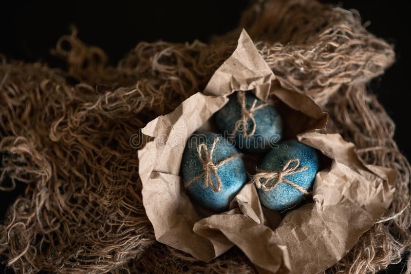 Easter eggs in nest painted by hand in blue color on dark background. Chicken and quail eggs catholic and orthodox easter holiday.  royalty free stock photography