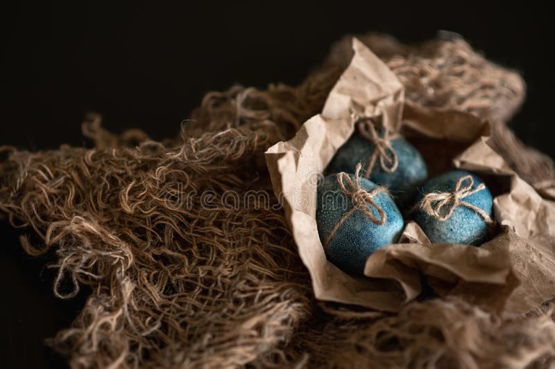 Easter eggs in nest painted by hand in blue color on dark background. Chicken and quail eggs catholic and orthodox easter holiday.  royalty free stock photos