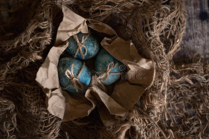 Easter eggs in nest painted by hand in blue color on dark background. Chicken and quail eggs catholic and orthodox easter holiday.  stock images