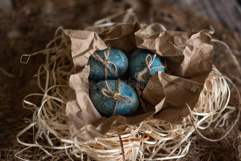 Easter eggs in nest painted by hand in blue color on dark background. Chicken and quail eggs catholic and orthodox easter holiday.  royalty free stock photo