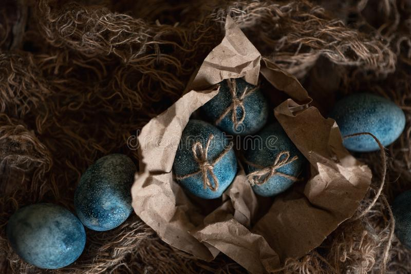 Easter eggs in nest painted by hand in blue color on dark background. Chicken and quail eggs catholic and orthodox easter holiday.  stock image