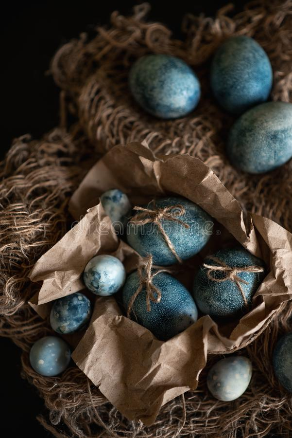 Easter eggs in nest painted by hand in blue color on dark background. Chicken and quail eggs catholic and orthodox easter holiday.  stock photos