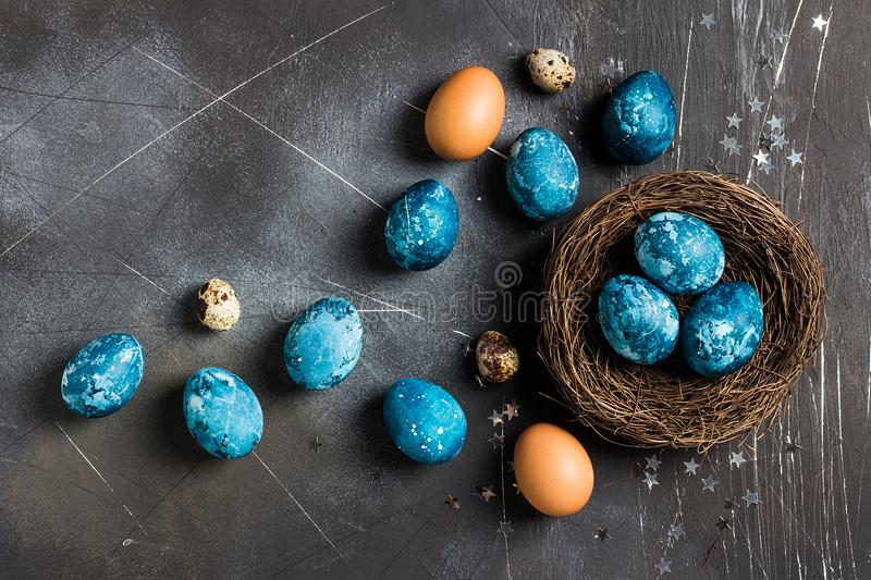 Easter eggs in nest painted by hand in blue color on dark background royalty free stock photography