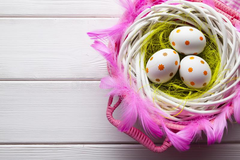 Easter eggs in the nest and pink basket on white table royalty free stock photos