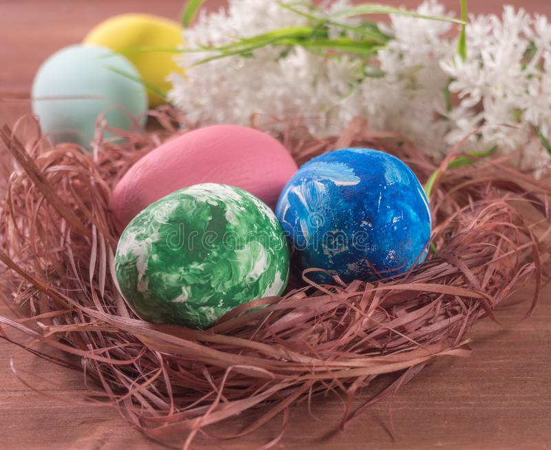Nest with Easter eggs and flowers on a wooden background. Easter background royalty free stock image