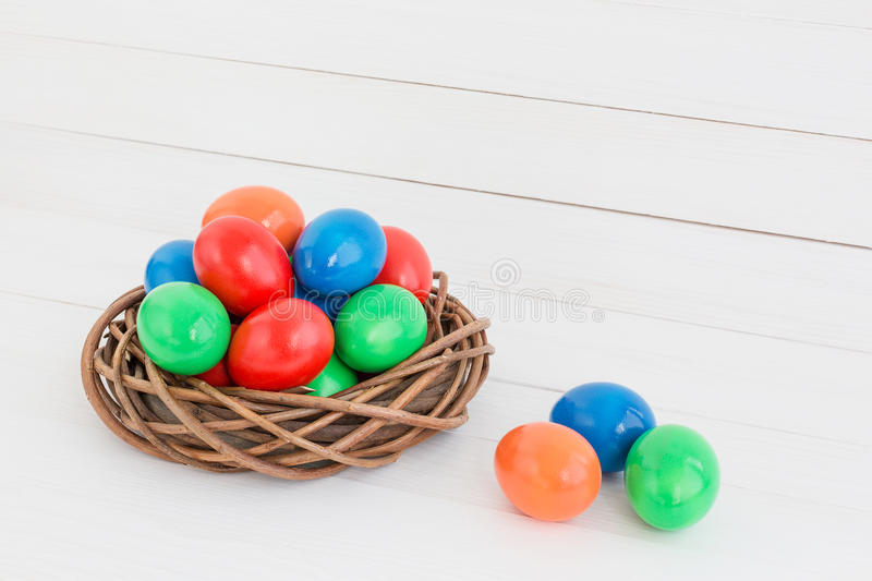 Easter eggs in nest on wooden background royalty free stock photography