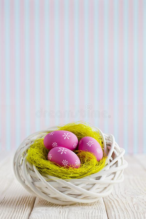 Easter eggs in the nest and wooden table on patterned background stock photos