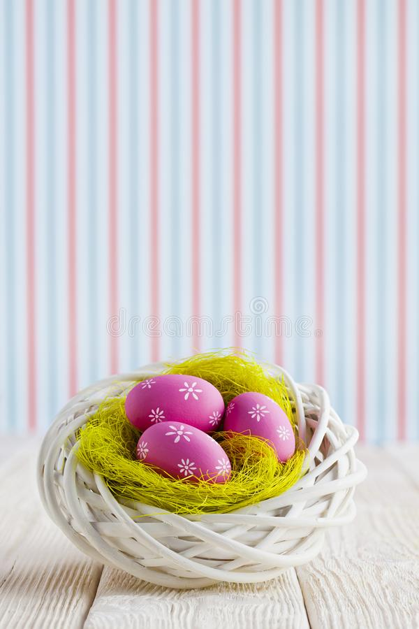 Easter eggs in the nest and wooden table on patterned background stock images