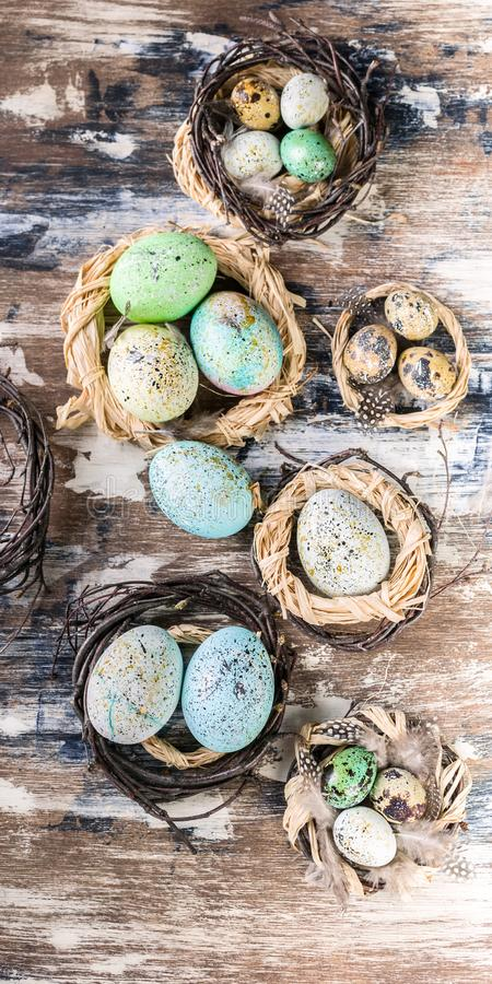 Easter eggs in nests. Easter decorations. Rustic surface. Vertical shot stock image