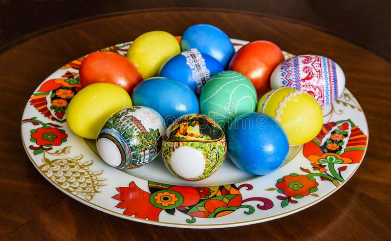 Easter eggs painted and painted in blue, red, yellow colored on a beautiful plate. royalty free stock images